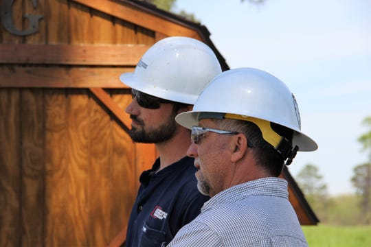 SWEPCO senior technical training specialist Brad Brown and lineman Colton Brown watch a training exercise at SWEPCO's Shreveport Training Center.