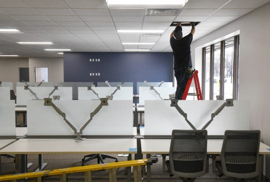 Workers put the finishing touches on the new St. Cloud Times office building Thursday, March 28, at 24 Eighth Ave. S in St. Cloud.
