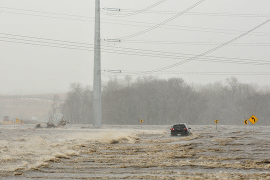 In this March 14, 2019, photo an abandoned car sits on Industrial Highway in floodwaters north of Norfolk, Neb. According to a trooper on scene, the occupant had to be rescued.