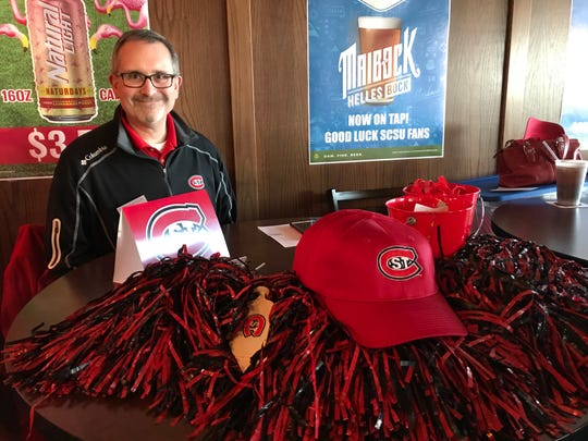 John Brown, St. Cloud State's associate director of alumni relations, shows off some of the merchandise he was handing out Friday at the Bulldog Tap in Fargo, North Dakota.