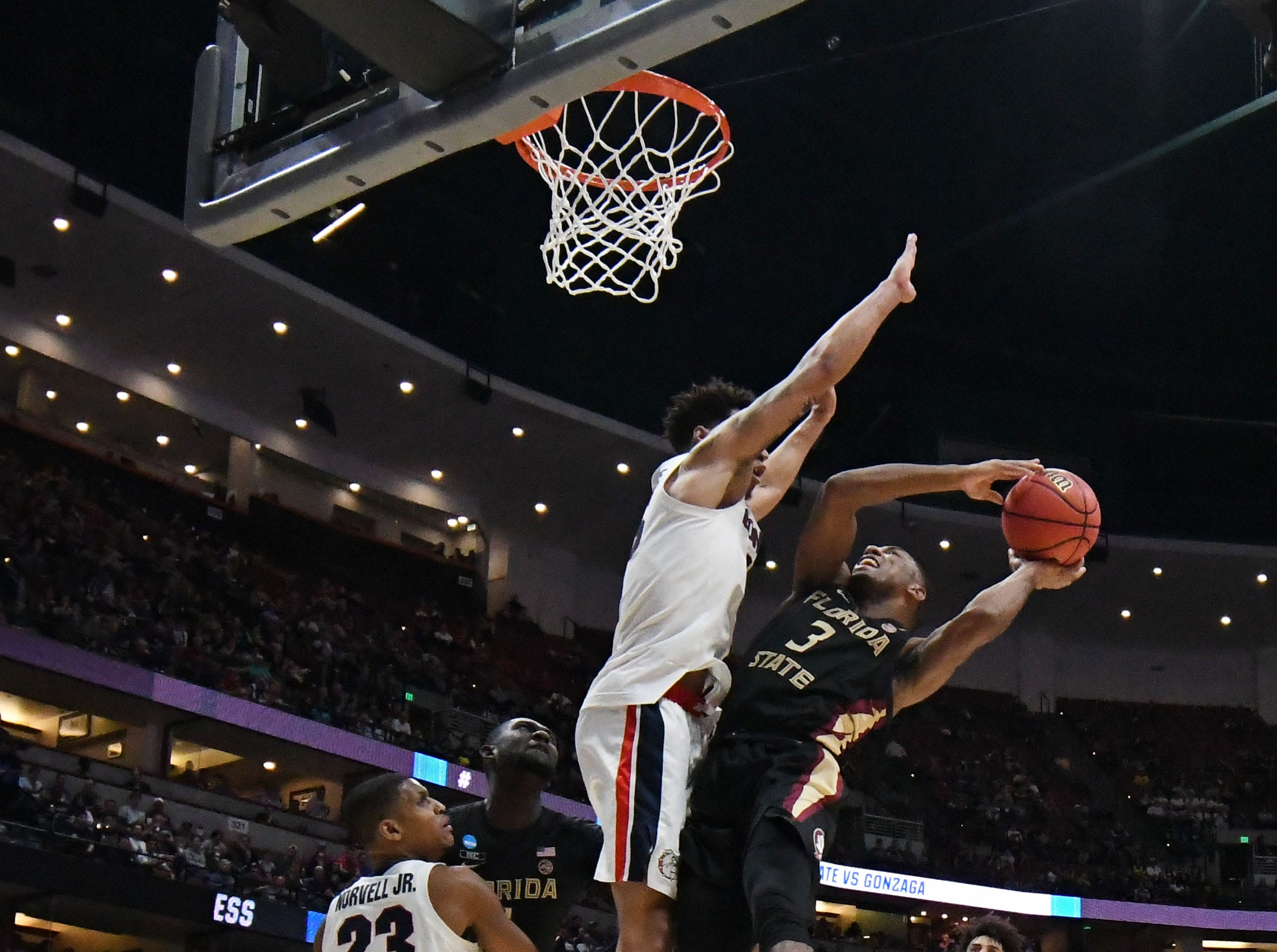 March 28, 2019; Anaheim, CA, USA; Florida State Seminoles guard Trent Forrest (3) moves to the basket against Gonzaga Bulldogs forward Brandon Clarke (15) and guard Zach Norvell Jr. (23) during the second half in the semifinals of the west regional of the 2019 NCAA Tournament at Honda Center. Mandatory Credit: Richard Mackson-USA TODAY Sports