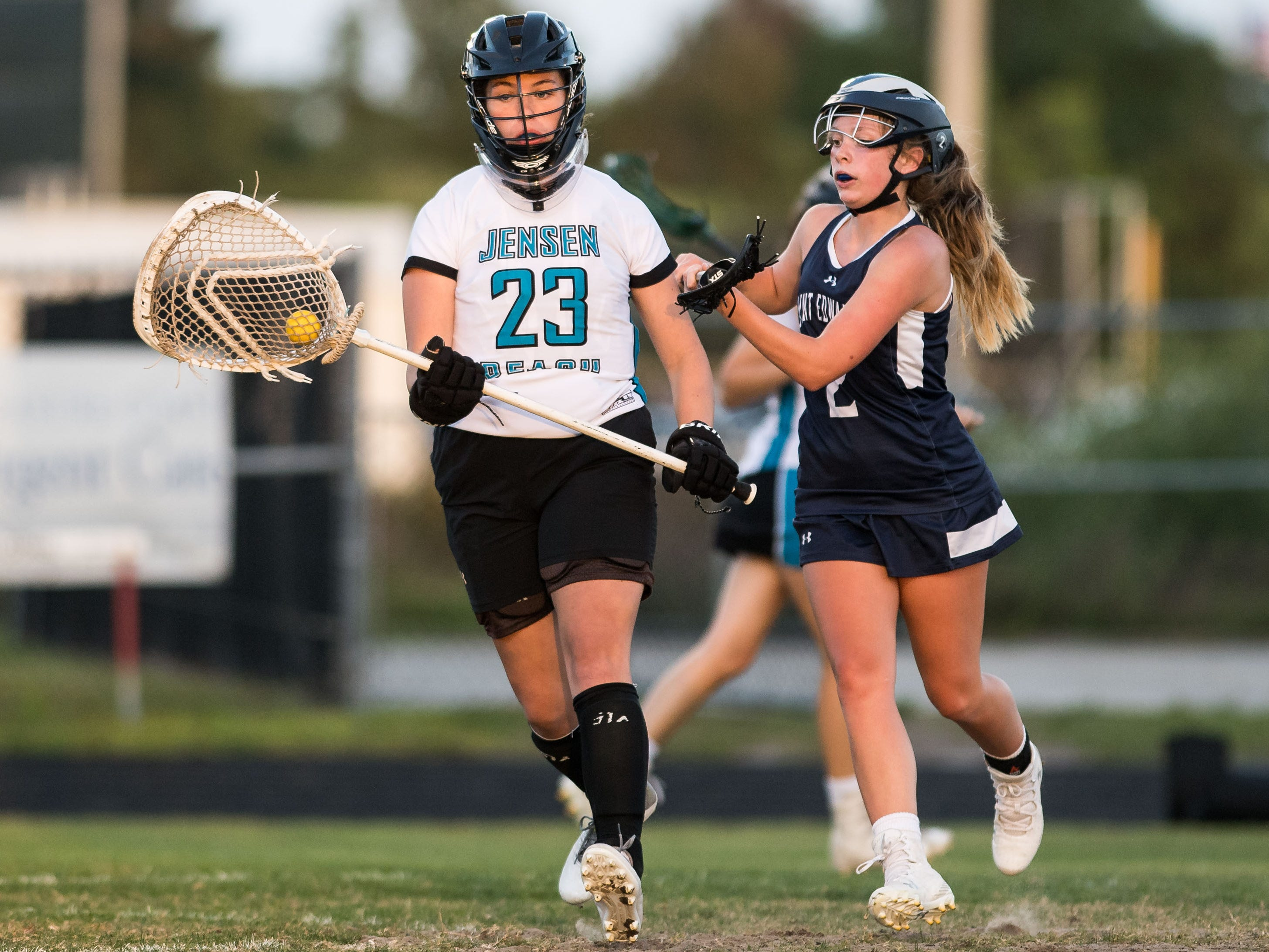 St. Edward's Molly McGee (right) pressures Jensen Beach goalkeeper Rachel Dionne after she saves a shot in the second half of the high school girls lacrosse game Thursday, March 28, 2019, at Jensen Beach High School.