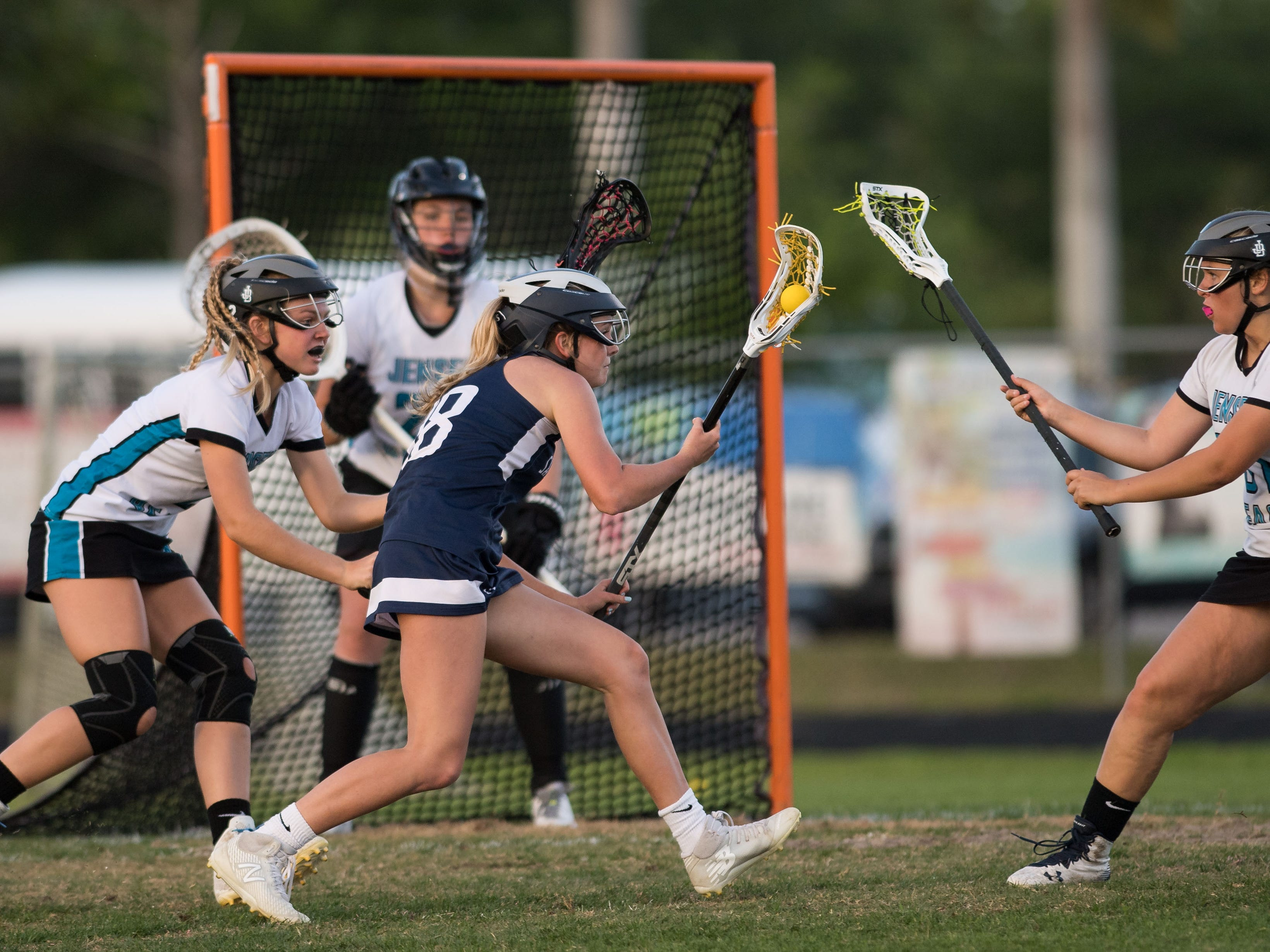 St. Edward's Bridget Nelson (center) maneuvers near the Jensen Beach goal, looking for an opening, in the second half of the high school girls lacrosse game Thursday, March 28, 2019, at Jensen Beach High School.