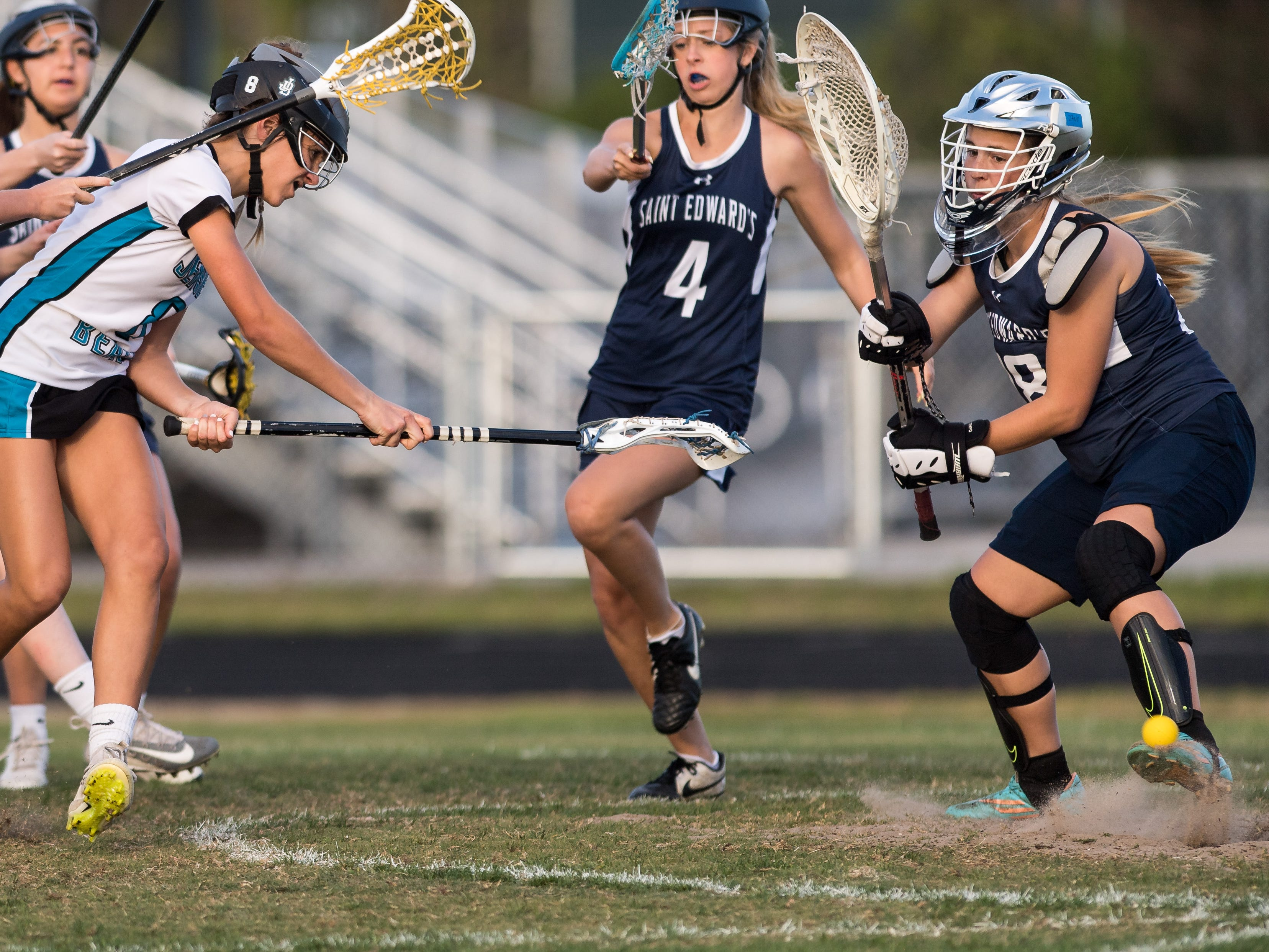 Jensen Beach's Faith Hamel (left) bounces a shot past St. Edward's goalkeeper Jane Callaghan to score in the second half at the high school girls lacrosse game Thursday, March 28, 2019, at Jensen Beach High School.