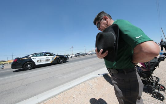 A mourner pays his respects Friday, March 29, 2019, during the funeral procession for El Paso County Sheriff's Deputy Peter Herrera, who was fatally shot during a traffic stop.
