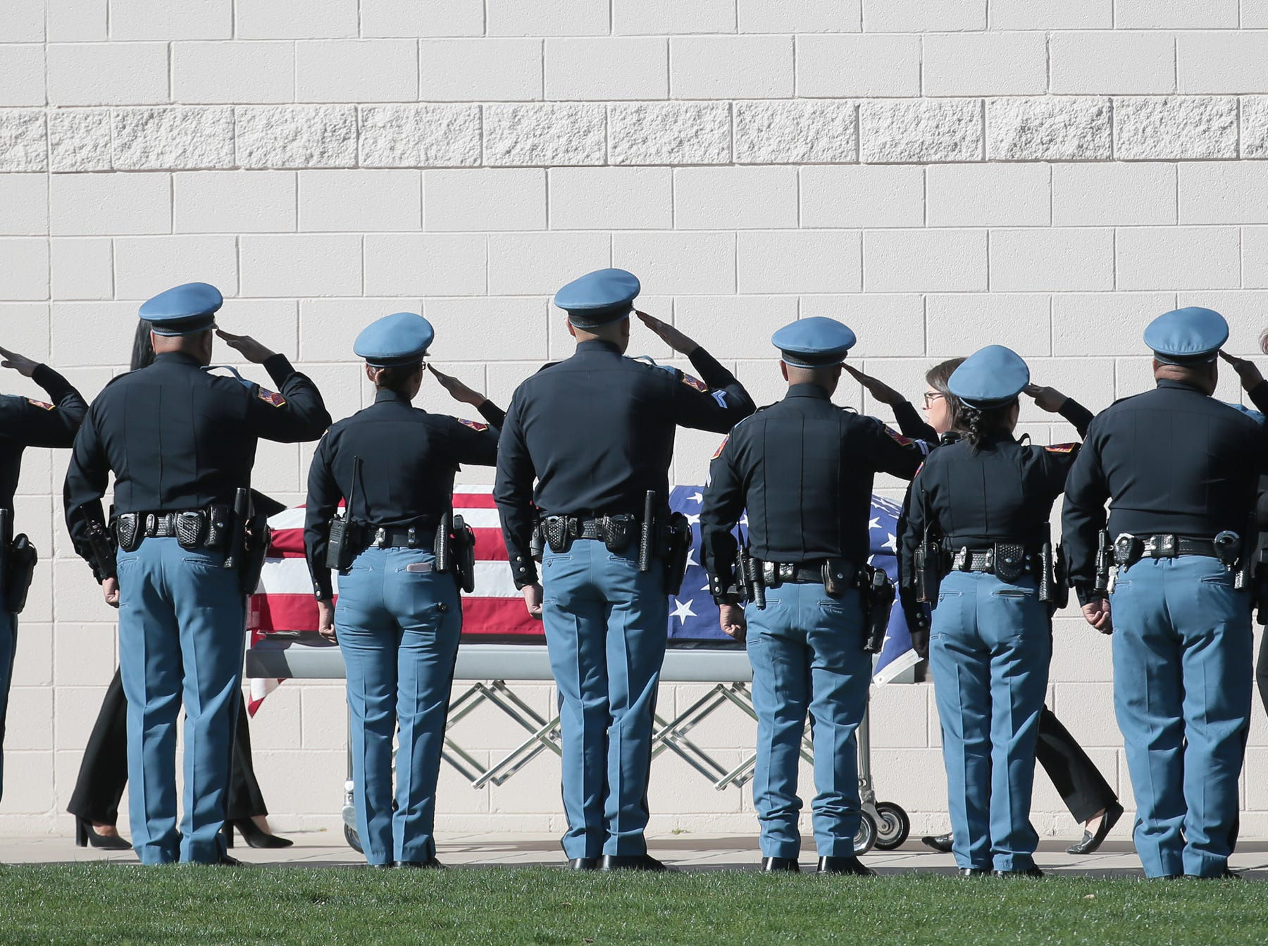 Police officers salute as El Paso County Sheriff's Deputy Peter Herrera's casket moves past at St. Frances Xavier Cabrini Catholic Church on Friday, March 29, 2019.