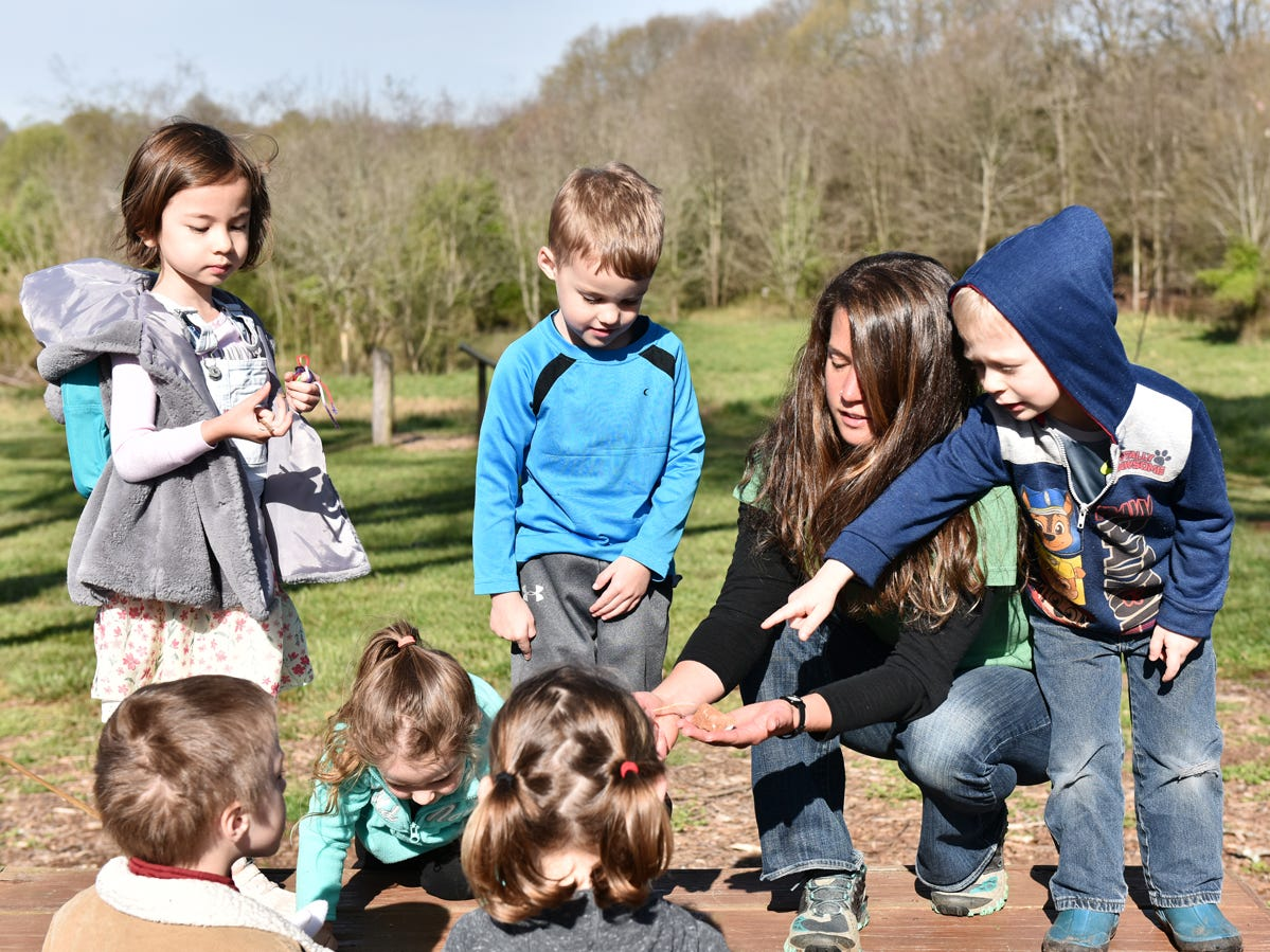 Children participating in the Knee High Naturalist program at Lake Conestee Nature Park look at items found on the ground and discuss which one will hit the ground first when dropped on Friday morning, March 29, 2019. The children were studying wind and wind resistance at part of the seasonal series. The Knee-High Naturalist program offers two 1.5 hour classes per month to pre-kindergarten students. There is a 6 class series offered each season except for winter.