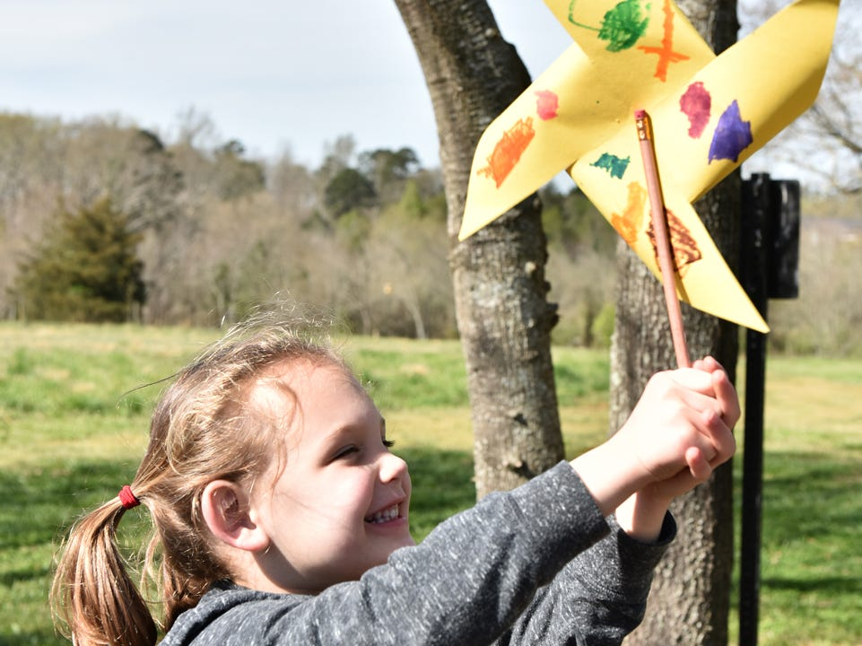A young girl holds up a pinwheel that she made during the Knee High Naturalists program at Lake Conestee Nature Park on Friday morning, March 29, 2019.