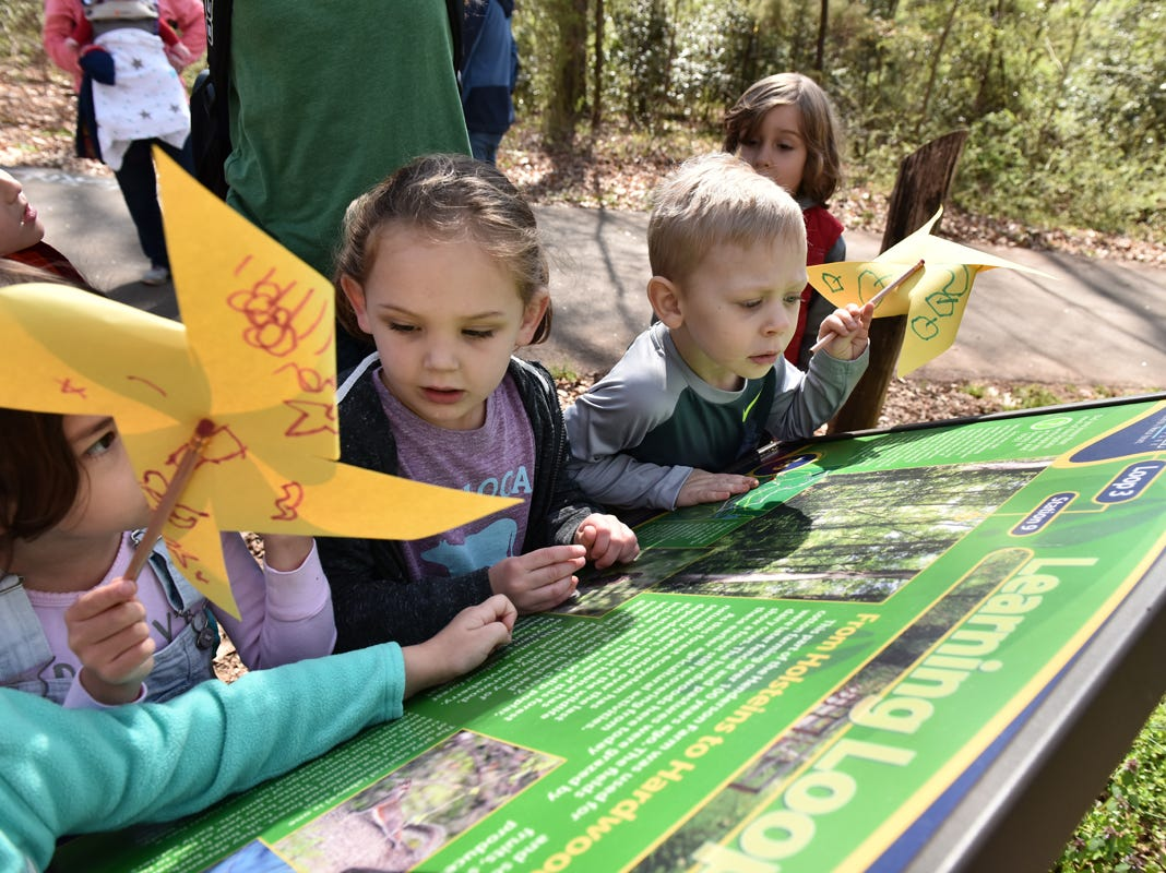 Children participating in the Knee High Naturalists program read signs along the trails at Lake Conesetee Nature Park on Friday morning, March 29, 2019.