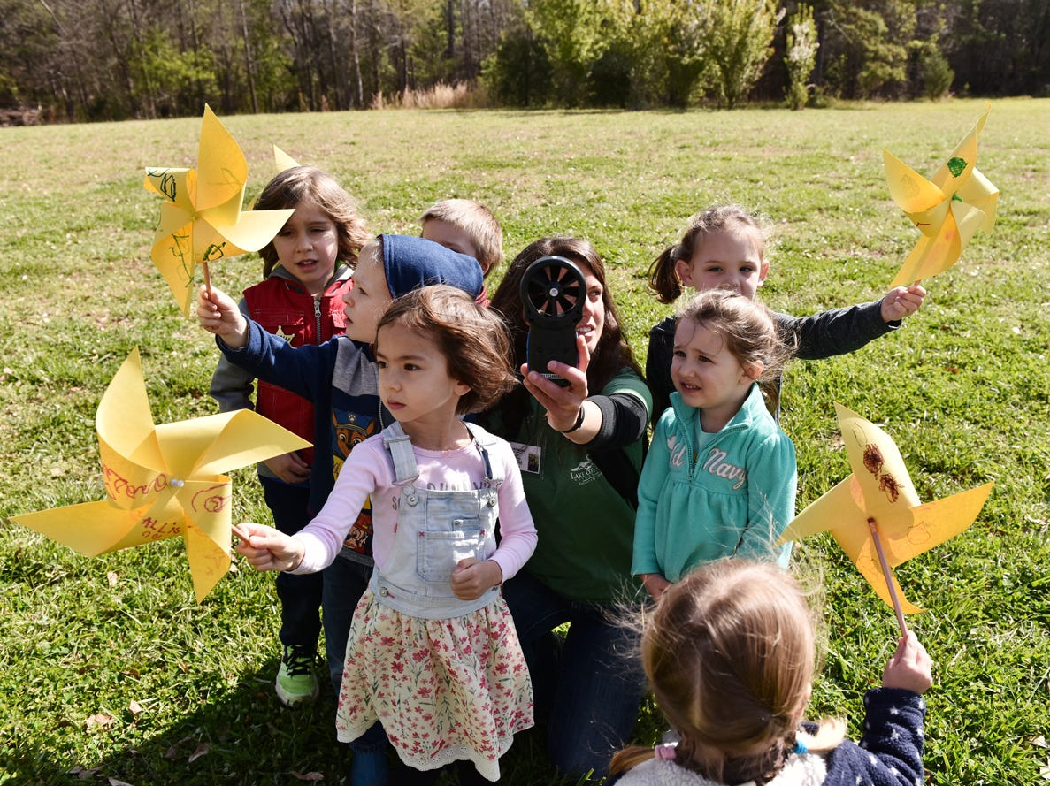 Taylor Phillips, middle, an educator at Lake Conestee Nature Park, uses an anemometer to measure wind speed as children hold up pinwheels they made during the Knee High Naturalist program at the park on Friday morning, March 29, 2019.