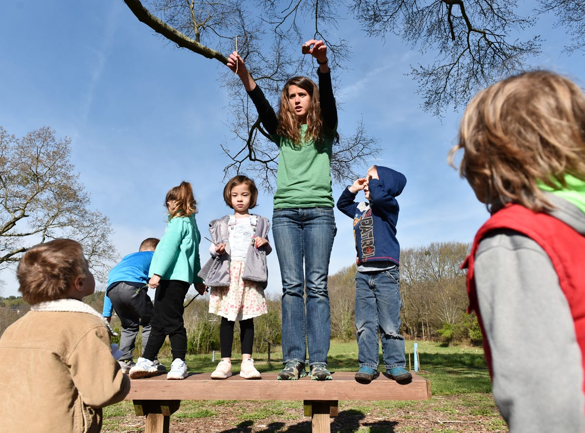 Taylor Phillips, middle, an educator at Lake Conestee Nature Park, drops items of different weights to demonstrate wind resistance during the Knee High Naturalists program at the park on Friday morning, March 29, 2019.