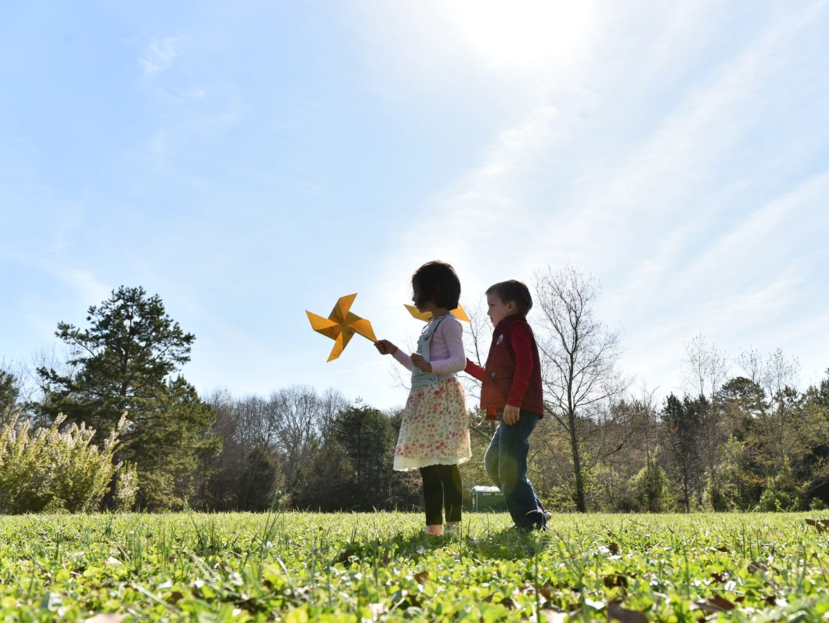 Children participating in the Knee High Naturalists program hold up pinwheels that they made at Lake Conestee Nature Park on Friday morning, March 29, 2019.