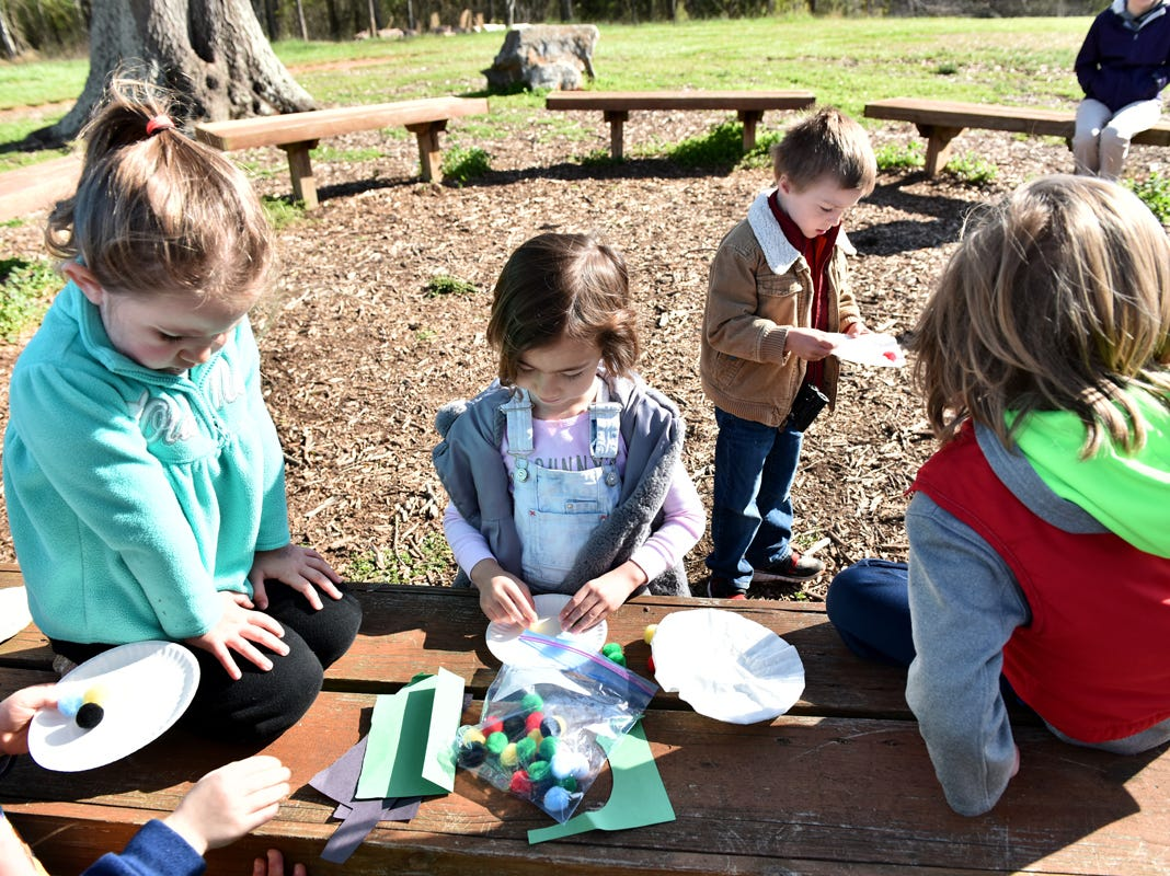 Children participating in the Knee High Naturalists program pick up different items to drop while learning about wind resistance at Lake Conestee Nature Park on Friday morning, March 29, 2019.