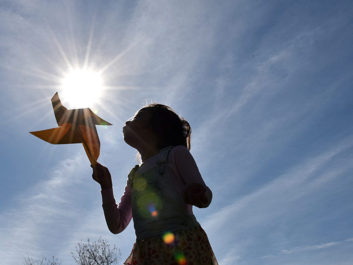 A young girl blows on a pinwheel that she made during the Knee High Naturalists program at Lake Conestee Nature Park on Friday morning, March 29, 2019.