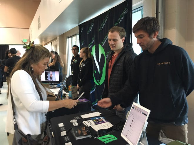 Employees with SafePort Cannabis Dispensary in Port Hueneme talk with attendees of a forum held Thursday on the state of the industry.