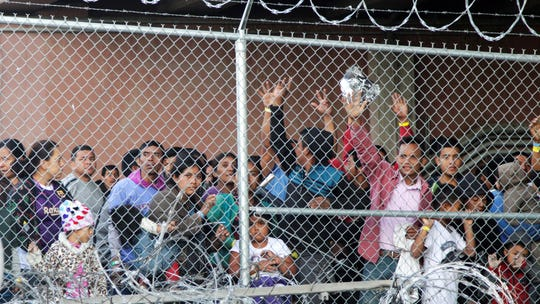 Central American migrants wait for food in El Paso, Texas, on Wednesday in a pen erected by U.S. Customs and Border Protection to process a surge of migrant families and unaccompanied minors.