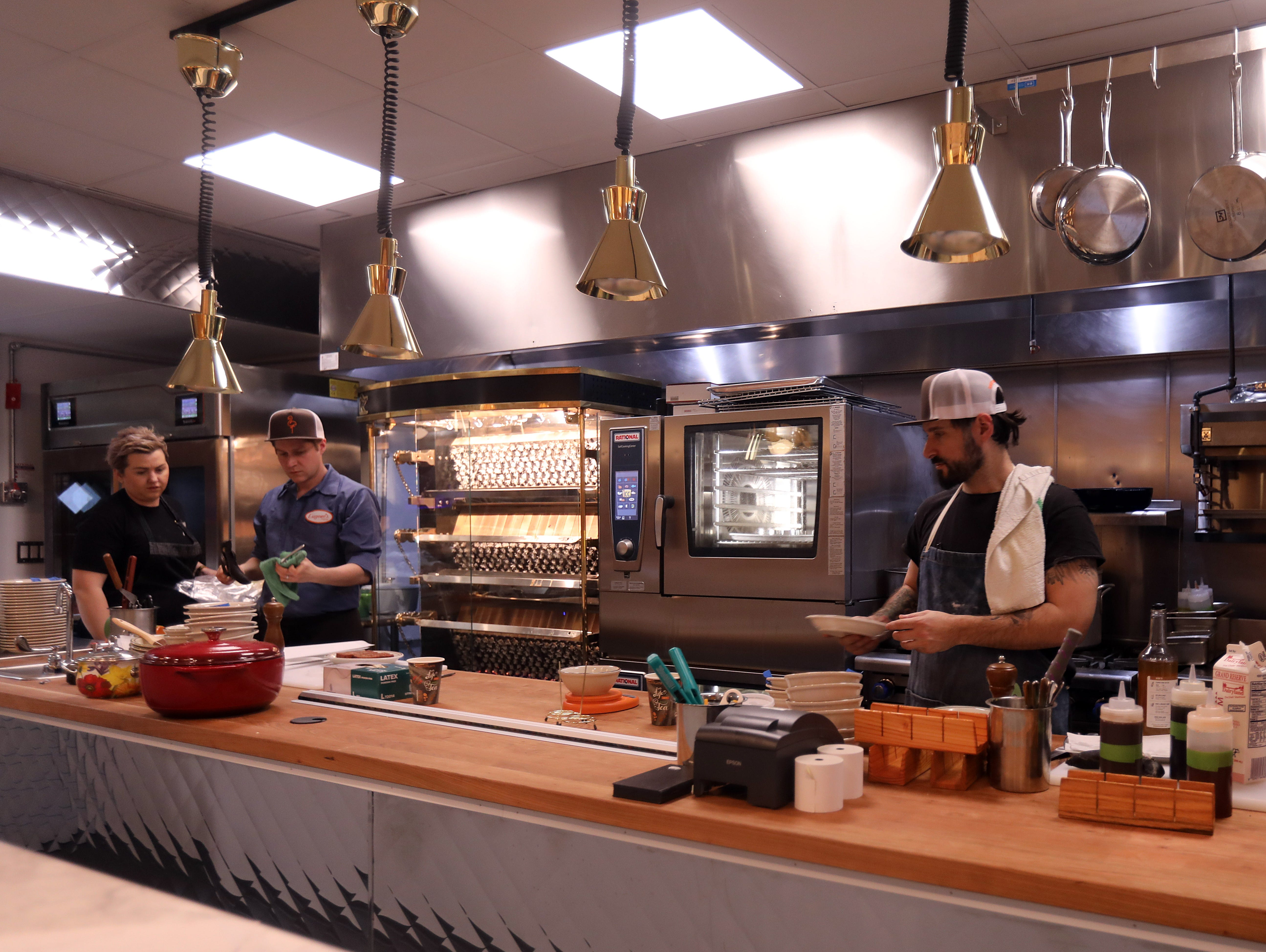 From left, John Poiarkoff, culinary director, Iulia Mahu, chef de cuisine, and David DiBari, owner are preparing food at at Eugene's in Port Chester March 29, 2019. The restaurant has a 70s-era basement vibe with wood panels, floral wallpaper, laminate counters, and their icon is a pink flamingo.