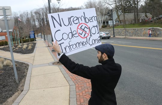Kevin Connery from Brooklyn holds a protest sign outside the Rockland County Office Building in New City in protest of the State of Emergency on Friday, March 29, 2019.