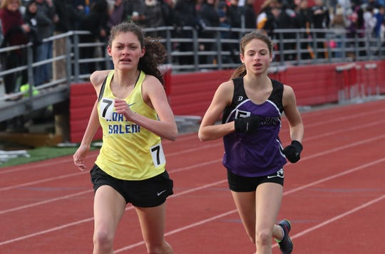 From left, North Salem's Ava Jolley edges out John Jay's Kelsey Crawford to win the girls mile during the Somers Tusker Twilight Relays at Somers High School  March 28, 2019.