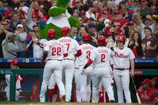 Phillies' Andrew McCutchen (22) Rhys Hoskins (17), Bryce Harper (3) and Jean Segura (2) celebrate after a Hoskins grand slam to take a 10-3 lead over the Braves Thursday at Citizens Bank Park.