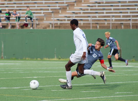 Old High's Marco Barron slide-tackles Palo Duro's Diyeme Meshak in the Region 1-5A bi-district playoff game.