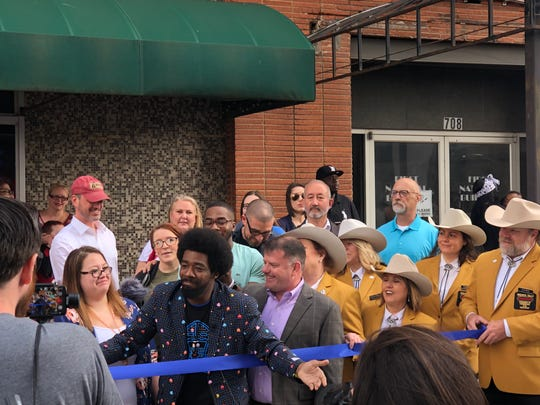 Marcus McGee, center, expressed his gratitude Friday for the community at the opening of his new business the Maniac Mansion arcade and cereal bar, 710 8th St.
