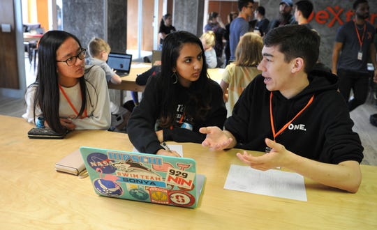 Hirschi High School students Lauren Nicolas, Sonya Ganeshram, and Nate Simmons work to bring a fictional Star War card game into reality during a hackathon held at the Dexter Learning Center, Friday morning.