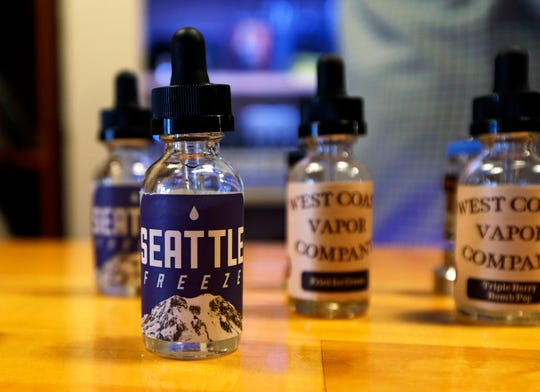 "This March 15, 2017, file photo shows vape liquids, including a brand named ""Seattle Freeze,"" displayed at the Future Vapor store in Seattle. Legislators in Washington state have approved a bill to raise the smoking and vaping age there to 21 on Wednesday, March 27, 2019, sending it to Gov. Jay Inslee for his signature. Supporters say the measure would help eliminate youth smoking, but at least one national anti-tobacco group has criticized its enforcement mechanisms."