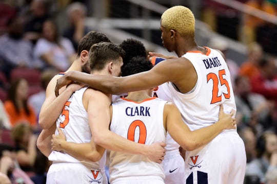 Virginia guard Kyle Guy (5) huddles with guard Kihei Clark (0) and forward Mamadi Diakite (25) during the first half in the semifinals of the south regional against the Oregon Ducks.