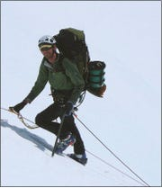 A climber ascending Alaska's Denali on fixed lines, with a Clean Mountain Can on his backpack. CMCs are used to safely transport human solid waste off the mountain.