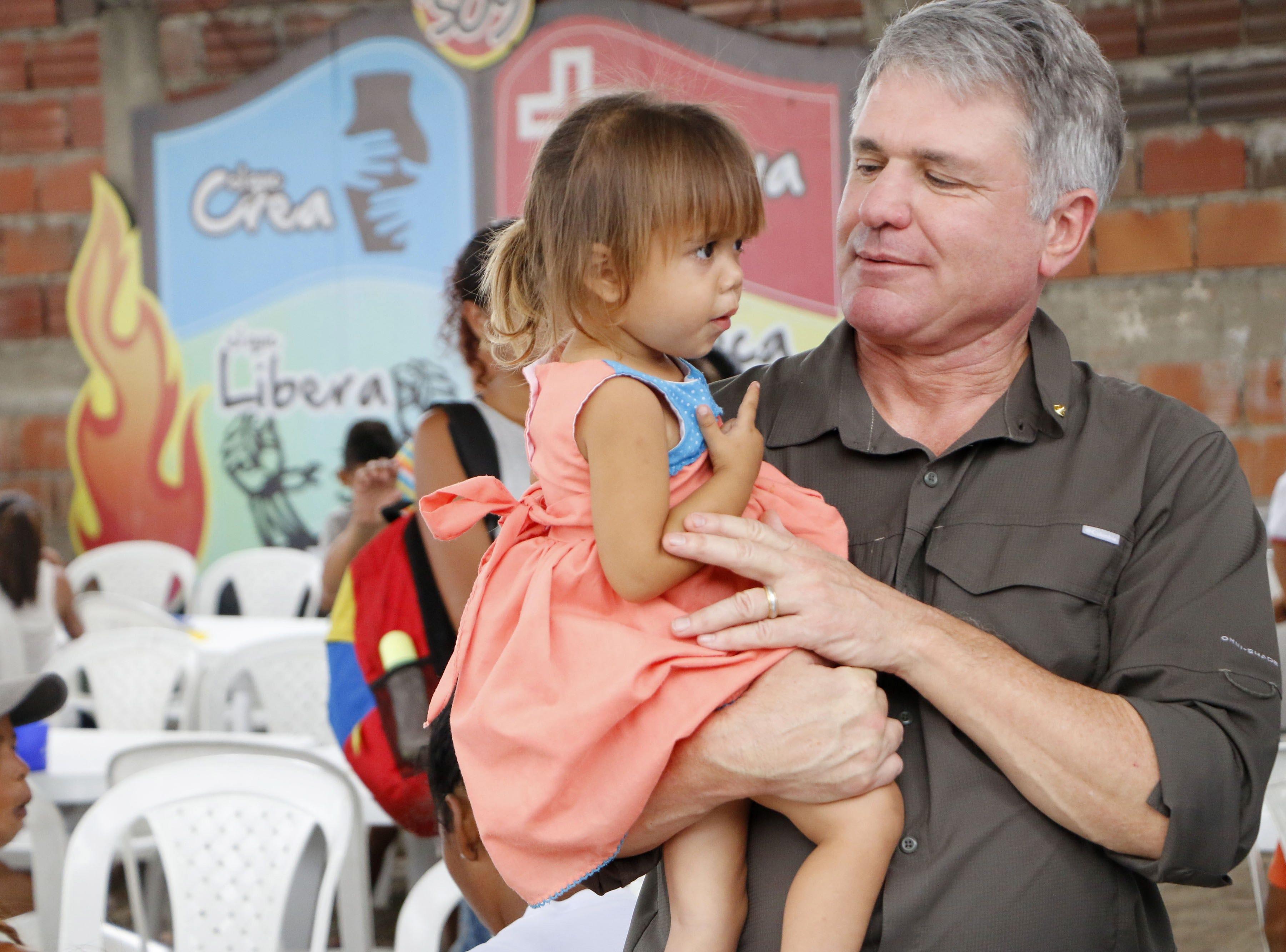 US Senator Michael McCaul holds a Venezuelan girl, during a hearing by several US senators on the Simon Bolivar international bridge, on the border between Venezuela and Cucuta, Colombia on March 29, 2019.