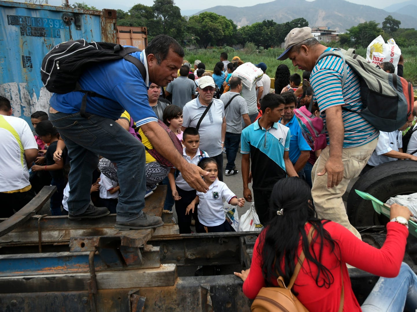 People cross the Simon Bolivar international bridge from Colombia into San Antonio del Tachira in Venezuela passing over the wreckage of a truck which was burned down during February 23rd protests, and containers placed by the Venezuelan government to block the entrance of the humanitarian aid to the country, on March 29, 2019. A group of approximately 100 people pushed the barriers placed by the Venezuelan Bolivarian Guard in the border town of San Antonio del Tachira and entered the country despite the restriction that allows only students, elderly people and patients under medical treatment in Colombia to cross the border.