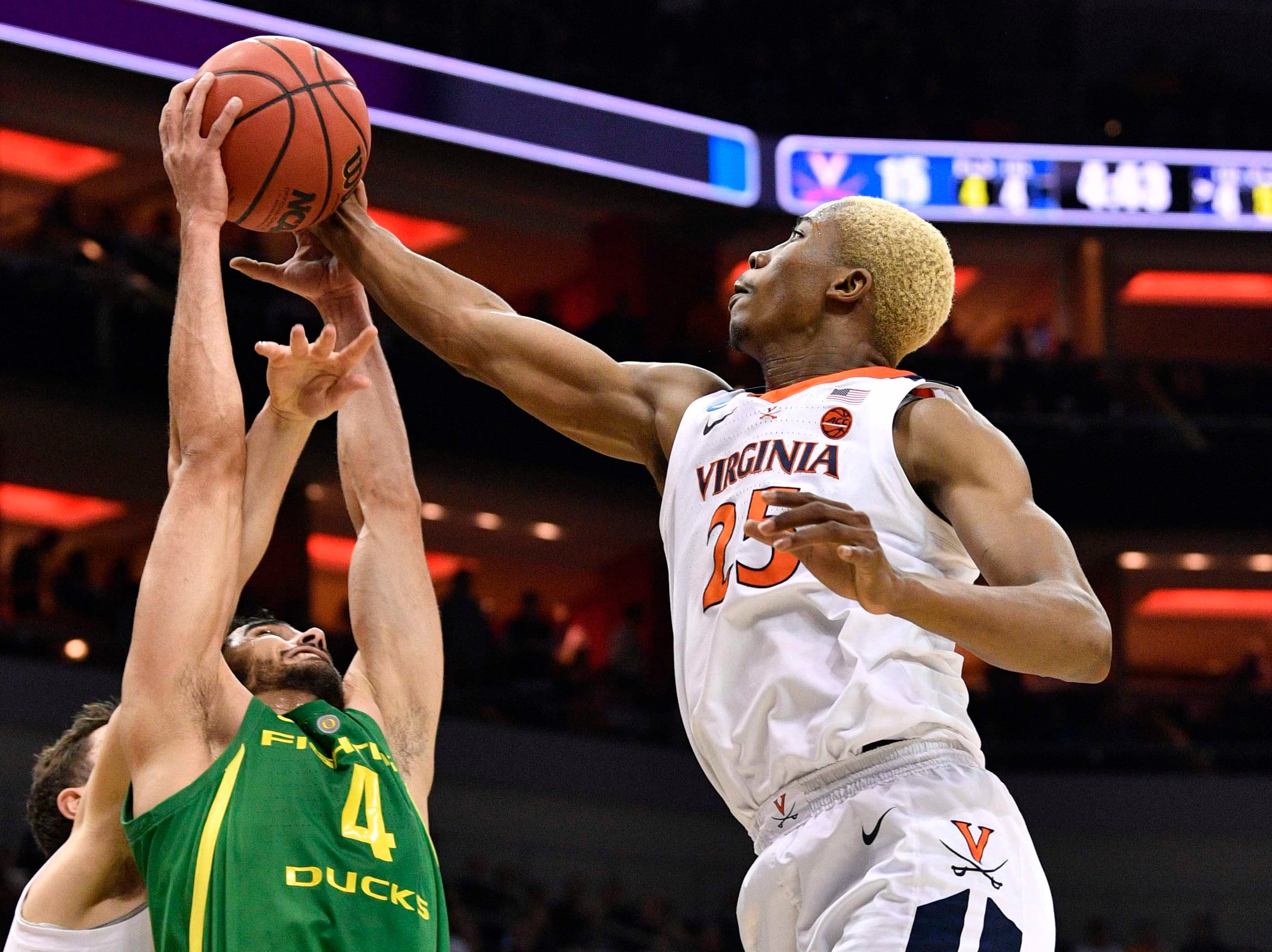 Sweet 16: Oregon Ducks guard Ehab Amin and Virginia Cavaliers forward Mamadi Diakite reach for the ball.