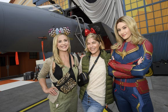 Sarah Michelle Gellar (left) and Selma Blair share a special moment with Captain Marvel at Disney California Adventure Park on March 28.
