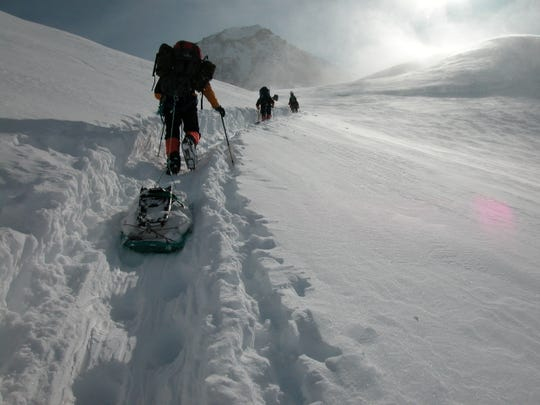 Climbers ascending Alaska's Denali, using sleds to carry their equipment.