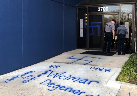 Law enforcement officers investigate racist and anti-Semitic graffiti in front of a building that houses the Oklahoma Democratic Party headquarters Thursday, March 28, 2019, in Oklahoma City.
