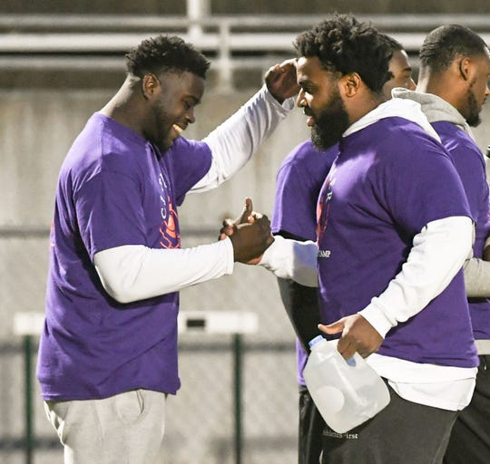 Shaq Lawson, left, current NFL Buffalo Bills, former D.W. Daniel and Clemson standout, shakes hands with former Clemson player Christian Wilkins, right, during the C.J. Fuller Foundation football camp at Easley High School Friday. Many former Clemson football players and former players from the area helped run drills and one-on-one challenges, with tips and encouragement.