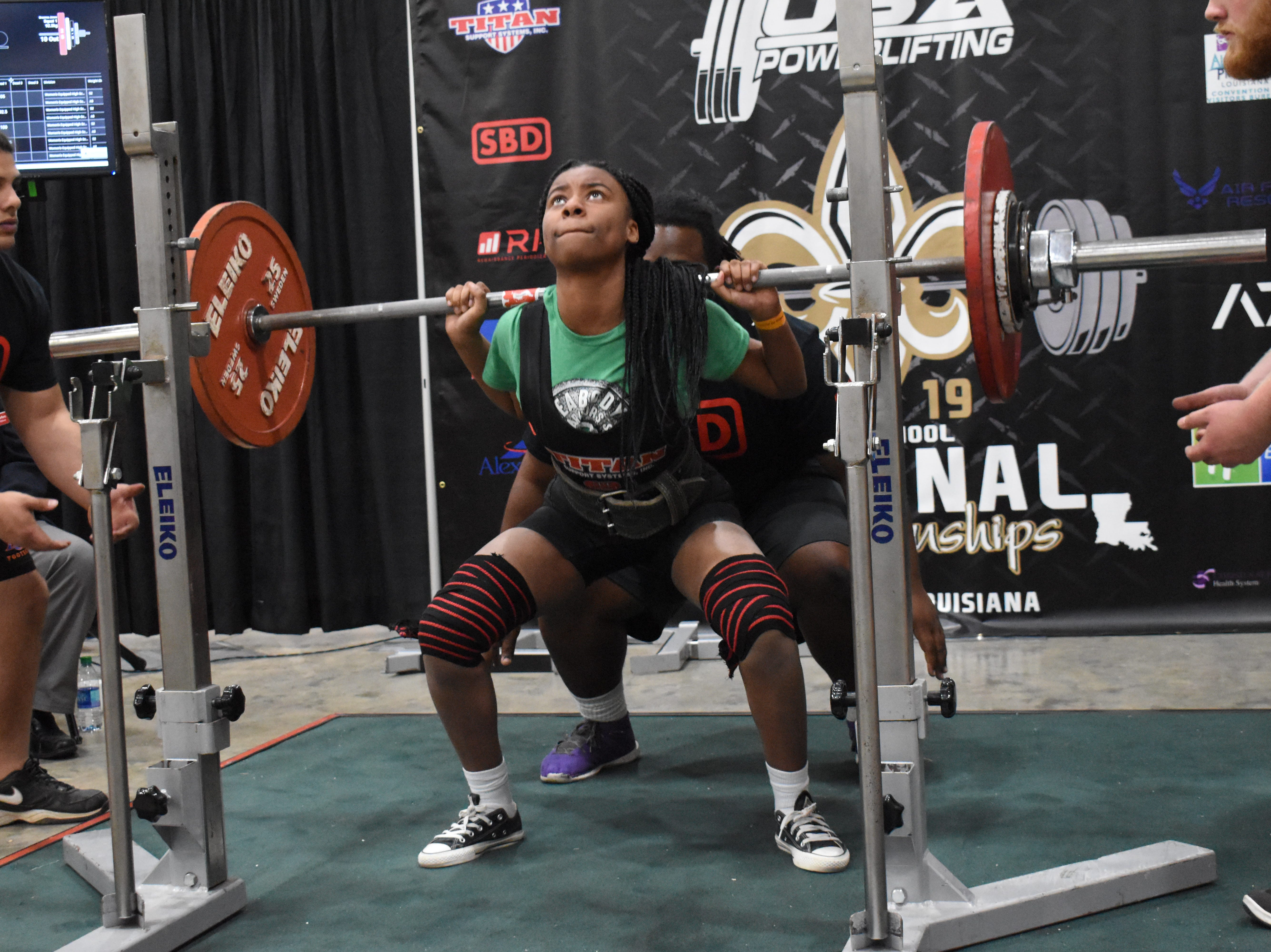 Breanna Jones of Peabody performs a squat in the The USA Powerlifting High School National Championships Friday, March 29, 2019. The championships, equipped and raw, are being held at the Randolph Riverfront Center in downtown Alexandria with high school powerlifters from across the country competing in the four-day event. Powerlifters from local schools are also competing.