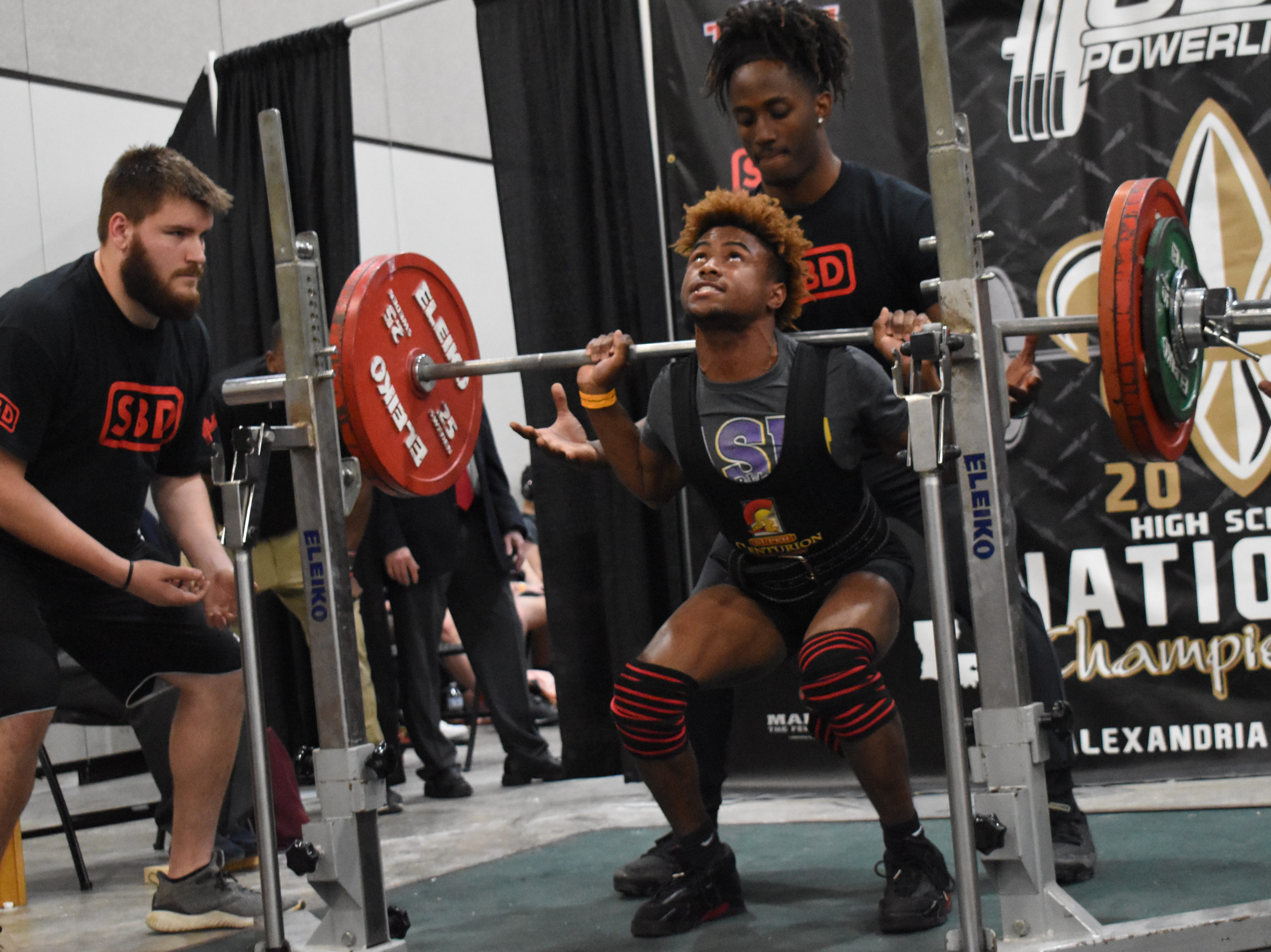 Freddie Price of Alexandria Senior High School performs a squat in the USA Powerlifting High School National Championships held Friday, March 29, 2019. The championships, equipped and raw, are being held at the Randolph Riverfront Center in downtown Alexandria with high school powerlifters from across the country competing in the four-day event. Powerlifters from local schools are also competing.