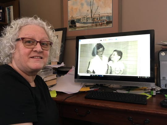 Alice Seccafino shows a slideshow of photos of her husband John, including this one of him as a 2-year-old polio patient.