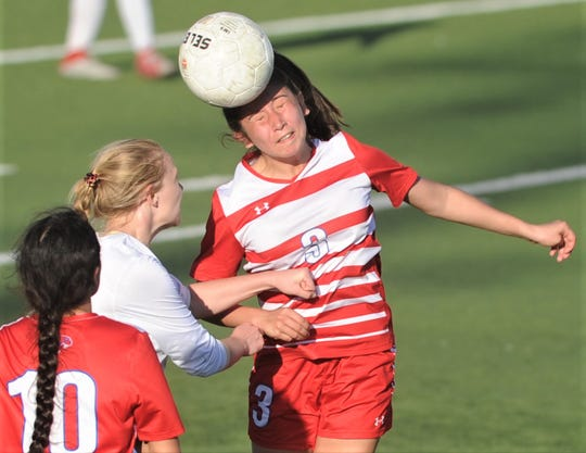 Cooper's Anessa Garcia (3) heads the ball over a Lubbock Coronado player as teammate Natalie Paredes (10) looks on. Coronado beat the Lady Cougars 4-1 in the Region I-5A bi-district playoff game Friday, March 29, 2019, at Tiger Stadium in Snyder.