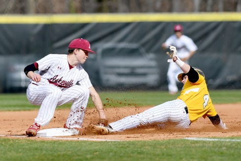 Asheville's Sam Duncan attempts to tag Tuscola's Hunter Bryson as he steals third base during their game at Asheville High School on March 29, 2019. Bryson was called safe at the base.