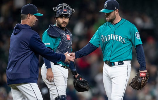 Seattle Mariners manager Scott Servais, left, pulls relief pitcher Hunter Strickland, right, from the game during the ninth inning after Strickland gave up a three-run home run to the Boston Red Sox's Mitch Moreland, Friday, March 29, 2019, in Seattle. The Red Sox won the game 7-6.