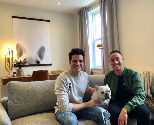 Eric Hillegass (left) and Patrick Bartscherer hang out with their French bulldog Griffin - who also appears in the print hanging on the wall behind them.