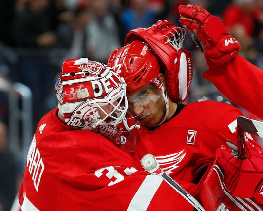 Red Wings goaltender Jimmy Howard, left, and Andreas Athanasiou celebrate the Wings' 4-0 win over the Devils on Friday, March 29, 2019, at Little Caesars Arena.