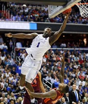 Duke forward Zion Williamson drives on Virginia Tech guard Ty Outlaw during the second half of an NCAA tournament East Region semifinal in Washington, Friday, March 29, 2019.