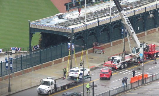 A white Chevrolet Traverse is placed on a hoist Saturday, March 30, 2019, to be put on display by General Motors at Comerica Park in Detroit, replacing the controversial red Blazer seen in front of the Traverse.