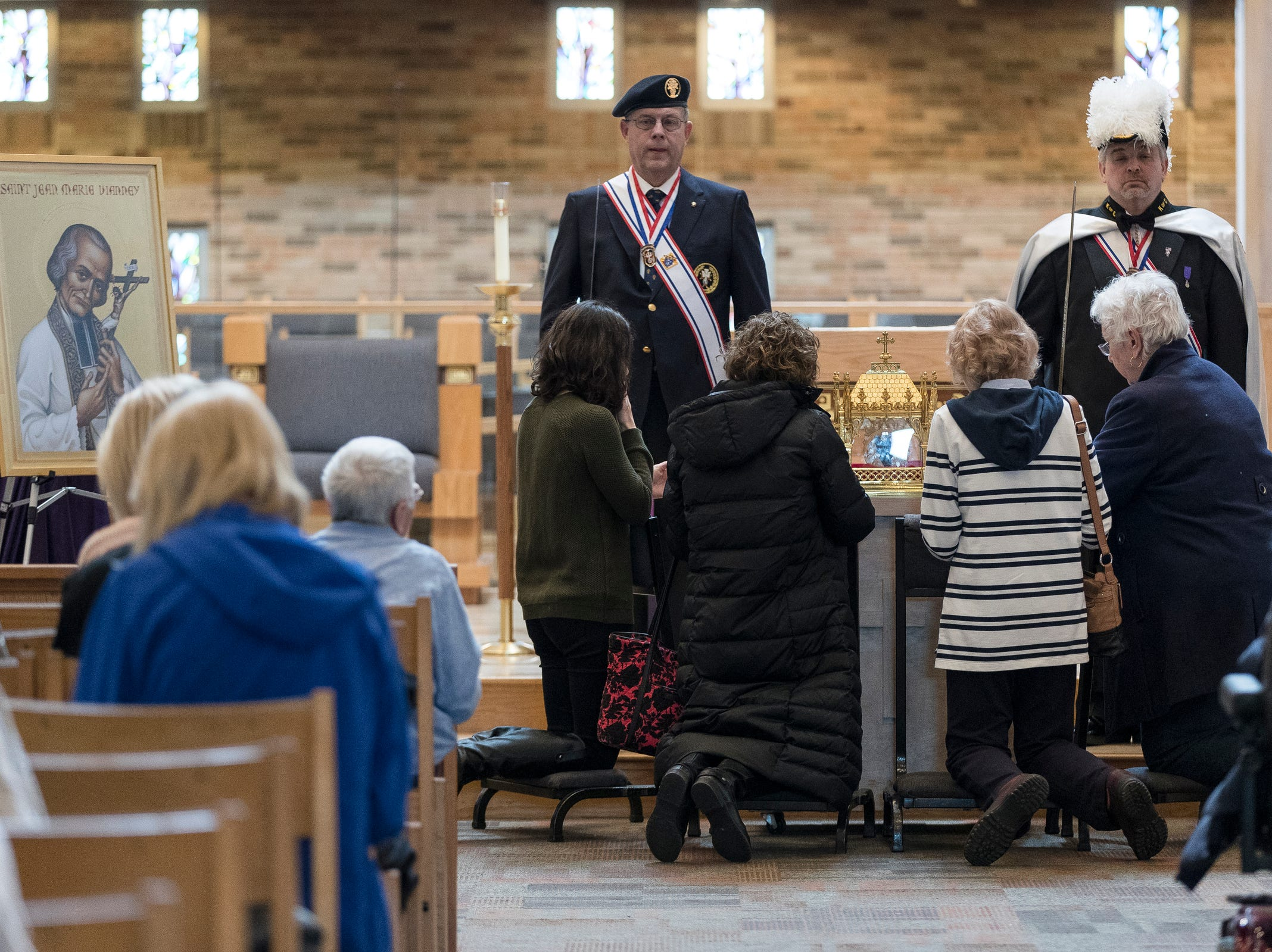 Pilgrims pray by the reliquary which contains physical heart of France's St. John Vianney during Heart of a Priest tour at St. John Vianney Parish in Shelby Township, Saturday, March 30, 2019.