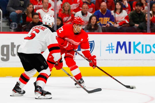 Red Wings center Andrew Athanasiou skates with the puck defendants Andy Greene in the second period on Friday, March 29, 2019, at Little Caesars Arena.