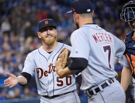 Tigers relief pitcher Reed Garrett celebrates his first Major League game with shortstop Jordy Mercer during the eighth inning of the Tigers' 6-0 loss to the Blue Jays on Friday, March 29, 2019, in Toronto.